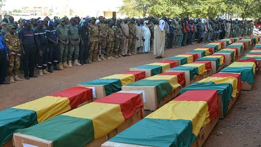 Showing coffins being honoured during a funeral ceremony in Mali.
