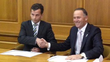 ACT MP David Seymour (left) signs a confidence and supply agreement with then-prime minister John Key.