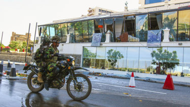 Sri Lankan soldiers ride past the bombed Kingsbury Hotel.