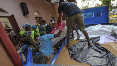 The bodies of victims are removed from St Sebastian's Church  in Negombo on Sunday.