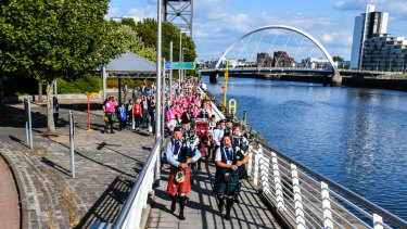 Delegates to the 2018 World Down Syndrome Congress in Glasgow are led along the Clyde river by the Dundee City Pipe Band.