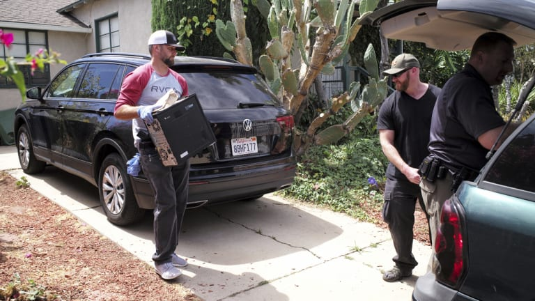FBI agents remove evidence from the home of Robert Chain in the Encino, Los Angeles, on Thursday.