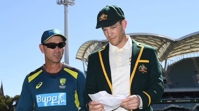 Long day ahead: Australian coach Justin Langer walks from the field with Tim Paine after losing the toss.