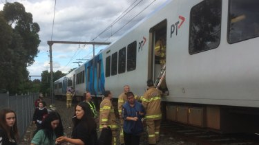 Firefighters assist passengers left stranded on carriages that separated from a moving train at Croydon.