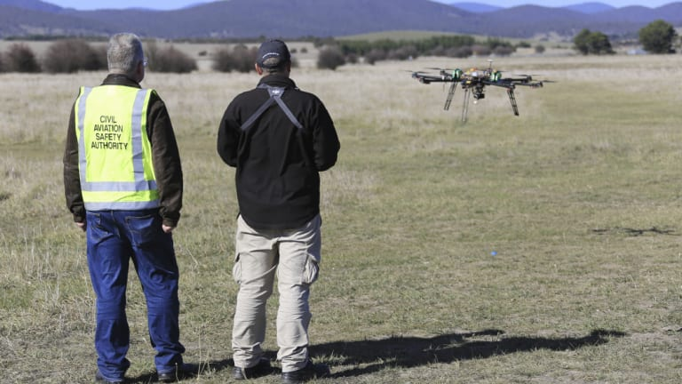 A CASA official watches a drone in flight.