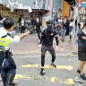 In this image from a video, a Hong Kong policeman holds on to one protester and prepares to shoot at another one, who was later hospitalised.