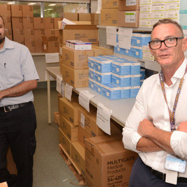 Rob Moloney (right) and PA Hospital nurse Gaurang Thakkar with some of the PPE stockpile.