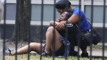 Two women cry outside the Stroger Hospital in Chicago on Sunday after they were asked to leave due to overwhelming crowds of family and friends of shooting victims.