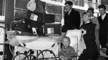 A British family wheel their luggage off a ship after arriving in Port Melbourne in February 1964.