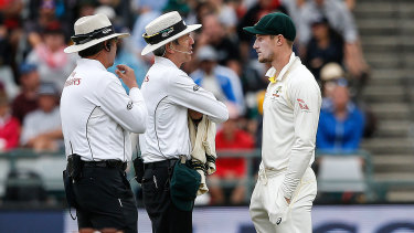 Caught: Umpires Richard Illingworth (left) and Nigel Llong confront Cameron Bancroft in Cape Town.