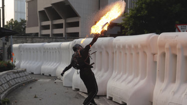 An anti-government protester throws a Molotov cocktail during a demonstration near the Central Government Complex in Hong Kong.