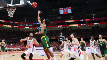 Patty Mills of Australia drives to the basket against Rudy Gobert of France.