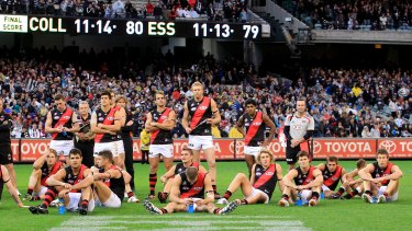 Bombed out: Shattered Essendon players ponder what might have been after going down by a point in an ANZAC Day classic.