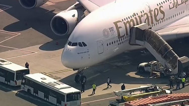 A person walks off the Emirates plane at JFK International Airport.