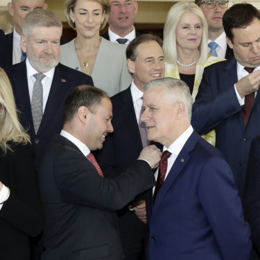 Members of the ministry put on Australian flag pins given to them by new Prime Minister Scott Morrison.