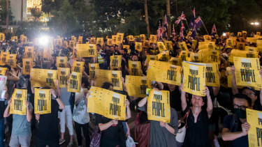 Demonstrators hold signs during the Stand with Hong Kong, Power To The People Rally at Chater Garden in Hong Kong, China.