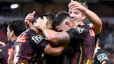Darius Boyd and the Broncos celebrate a try on Friday night.