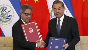 El Salvador's Foreign Minister Carlos Castaneda, left, and China's Foreign Minister Wang Yi shake hands at a signing ceremony to mark the establishment of diplomatic relations.