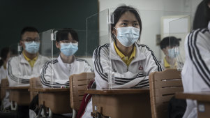 Senior students study in a Wuhan classroom with shields on each desk as a protection against coronavirus. About 57,800 students in their final year went back to school on Wednesday in Wuhan.