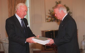 Commissioner James Staunton (left) hands the CAA and Seaview Air Commission of Inquiry report to the Governor-General Sir William Deane at Government House in Canberra in 1996.