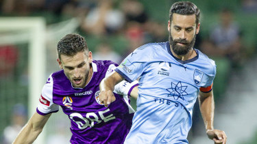 Matthew Spiranovic tackles Sydney FC's Alex Brosque in Perth on Wednesday night.