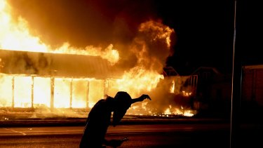 A protester walks past a building set on fire during protests against the police shooting of Jacob Blake in Kenosha on Monday.