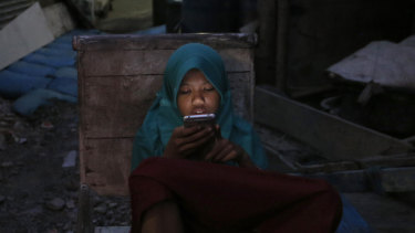A girl checks her mobile phone at a slum in Jakarta. Poverty afflicts close to a tenth of Indonesia's nearly 270 million people.