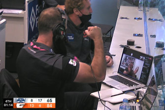 Adam Schneider celebrates from afar with the GWS coaches at the ground.