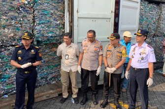Indonesian police and customs officials display the contents of containers full of waste they say will be sent back to Australia.