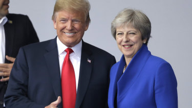 US President Donald Trump, left, talks to British Prime Minister Theresa May during a summit of heads of state and government at NATO headquarters in Brussels on Wednesday.