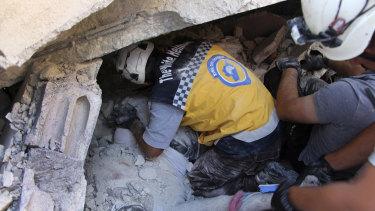 Rescuers remove a body from the rubble at the scene of the explosion in Sarmada, Idlib.