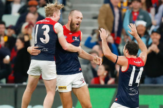 Clayton Oliver, left, Max Gawn and Michael Hibberd celebrate Melbourne's win over Hawthorn on Sunday.