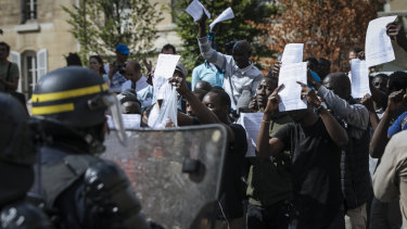 Migrants shouts hold up papers with a list of their demands and shout at police outside the Pantheon in Paris.