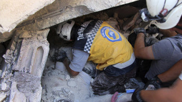 Rescuers remove a body from the rubble at the scene of the explosion in Sarmada, Idlib.