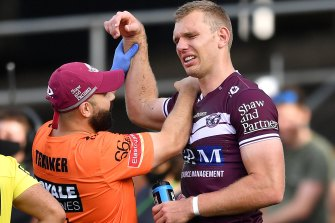 Tom Trbojevic grimaces while having his shoulder assessed after injuring it against the Titans.