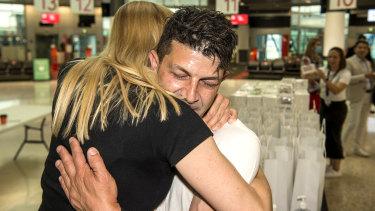 Genevieve Wild and Adam De Guara embrace at the airport.