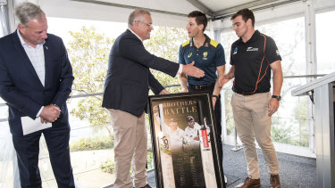 Prime Minister Scott Morrison accepts a gift from the Australian cricket captain Tim Paine and the Black Caps vice-captain Tom Latham at Kirribilli House.