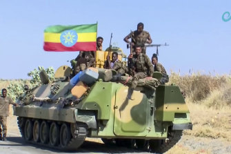Ethiopian military sit on an armuored personnel carrier next to a national flag, on a road near the border of the Tigray and Amhara regions of Ethiopia.