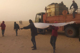 Migrants wait for help in the Libyan Sahara near the border with Sudan. Authorities in southern Libya have accelerated expulsions of migrants to Sudan and Chad during the coronavirus pandemic.
