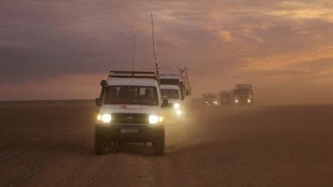 A convoy of vehicles of the Syrian Arab Red Crescent takes aid supplies across the Syrian desert to Rukban camp between the Jordan and Syria borders in 2018.