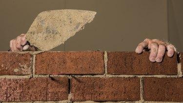 Artist Mitch Cairns building a red brick wall.