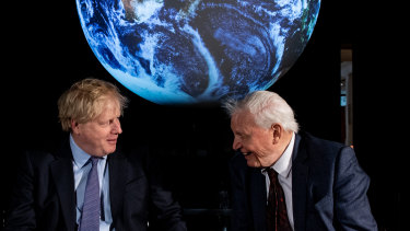 British Prime Minister Boris Johnson and British broadcaster and naturalist Sir David Attenborough speak with school children during the launch of the UK-hosted COP26 UN Climate Summit in Glasgow.