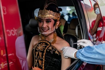 A woman wearing Javanese traditional costume receives a dose of the Sinovac (CoronaVac) vaccine at a drive-thru vaccination spot in a temple complex in Yogyakarta, Indonesia.