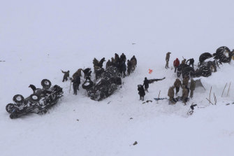 Rescuers dig in the snow around at least three overturned vehicles following the second avalanche.