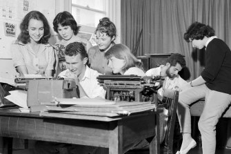 Clive James typing the University of Sydney's issue Honi Soit while, from left, Marie Taylor, Jane Iliff, Madeleine St John and Sue McGowan watch him as the editor, David Ferraro, and Helen Goldstein plan other pages on February 23, 1960.