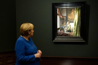 """German Chancellor Angela Merkel looks at """"Girl Reading a Letter at an Open Window"""", in which a cherub has been recently revealed in the top-right corner. Experts deduced that it was painted over long after Vermeer finished with the work."""