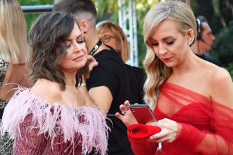 Lisa Wilkinson and Carrie Bickmore keep an eye on social media before launching on to the Logies red carpet last Sunday.