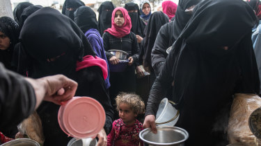 Displaced Syrians wait for hot meal distributed in Idlib.