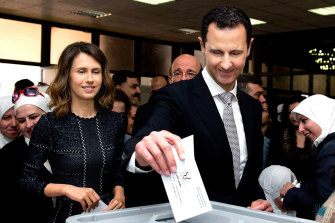 Syrian President Bashar al-Assad, pictured casting his ballot in parliamentary elections in 2016, as his wife Asma, left, looks on.