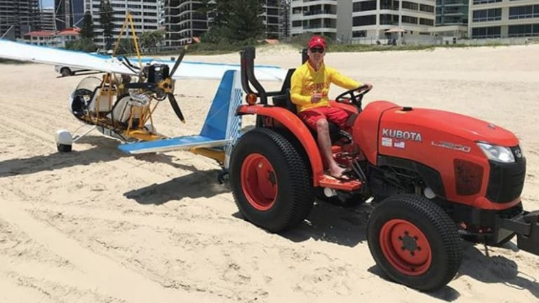 The stricken glider is towed off the beach by surf lifesavers on Saturday.